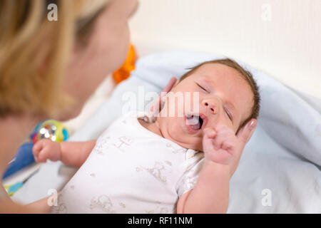 Young mother hugging her newborn child. Mom nursing baby. Family at home. Love, trust and tenderness concept. - Stock Photo