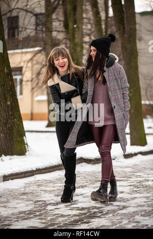 Young stylish women walks in the snowy park, recreation. Warm and comfortable winter clothes. - Stock Photo