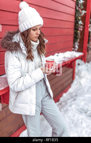A beautiful and young girl is warming about a mug, holding cup with hot coffee or tea in her hands. In a warm white winter hat and casual clothes. On the background of red and snow-covered houses. - Stock Photo