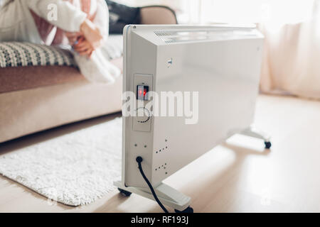 Using heater at home in winter. Woman warming body sitting on sofa by device. Heating season. - Stock Photo