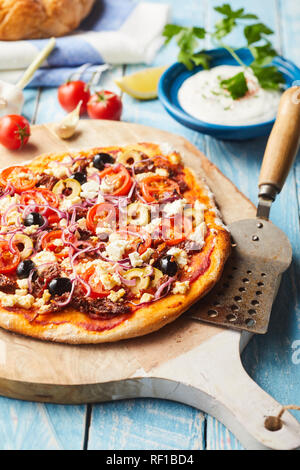 Whole Greek pizza with a thin crusty base topped with tomato, olives and feta cheese on an old wooden chopping board with spatula - Stock Photo