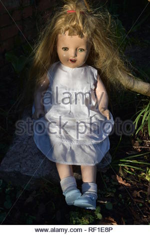 Creepy old antique doll scary long blond hair staring eyes in a white dress outdoors in a wood with trees - Stock Photo
