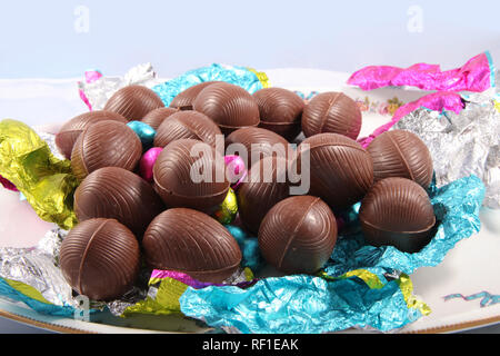 Pile of unwrapped chocolate easter eggs with the colourful foil wrapping surrounding it on a white background. - Stock Photo