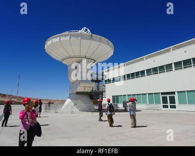 Alma Observatory, Atacama Desert, Chile; 01 24 2016: Tourists visit one of the radio telescopes of the the Atacama Large Millimeter Array - Stock Photo