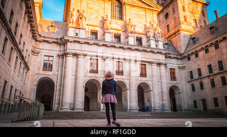 A young woman, tourist in a hat is standing in front of the basilica at El Escorial palace and monastery at the San Lorenzo de El Escorial at sunset - Stock Photo