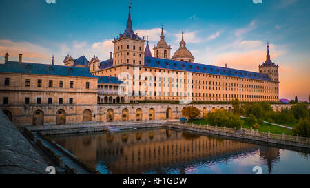 Sunset behind the beautiful El Escorial palace and monastery at the San Lorenzo de El Escorial with the Frailes Garden and reflections in the pond. - Stock Photo