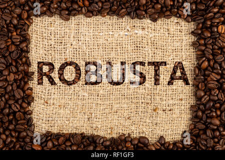 Robusta coffee type spelled inside frame made out of scattered beans on brown textured background - Stock Photo