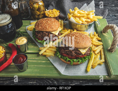 Burger pulled beef barbeque , sandwich, french fries, sauce, dark beer, corn, on a wooden tray - Stock Photo