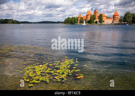 Trakai Island Castle in Lithuania, Eastern Europe. Tourists visit city castle. - Stock Photo