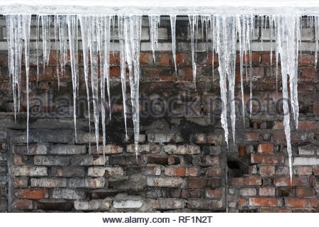 Icicles hanging from roof of the building, water drips from them/copy space/fall icicles,sudden warming,сold winter, poor thermal insulation. - Stock Photo