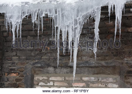 Cropped huge icicles hanging from roof of the building/ fall icicles, dangerous situation, сold winter, poor thermal insulation, ice stalactite. - Stock Photo