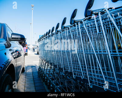 Supermarket shopping carts in a row in large supermarket store parking near black car - Stock Photo