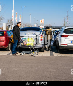 KARLSRUHE, GERMANY - FEB 24, 2018: Eastern ethnicity family couple loading groceries in Kaufland supermarket food parking - Stock Photo