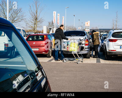 KARLSRUHE, GERMANY - FEB 24, 2018: Middle Eastern ethnicity family couple loading groceries in Kaufland supermarket food parking  - Stock Photo