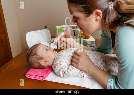 Mother using the nasal aspirator with her baby - Stock Photo