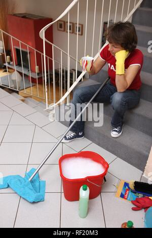 House work, woman having a coffee break during house cleaning - Stock Photo