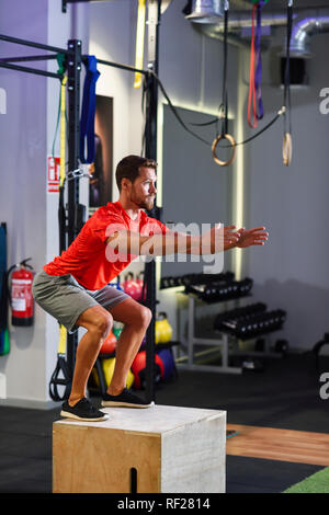 Man doing box jumps in a gym - Stock Photo