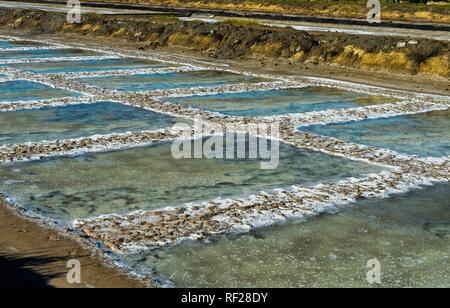 Sea salt extraction, evaporation basin of a sea water saline with crystallized sea salt, Tavira, Algarve, Portugal - Stock Photo