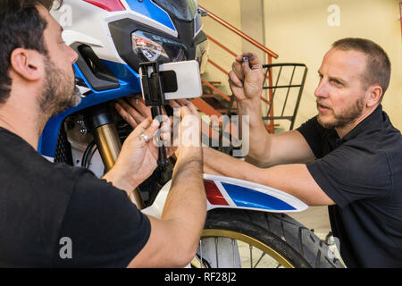 Mechanic working on motorcycle in workshop filmed by his partner - Stock Photo