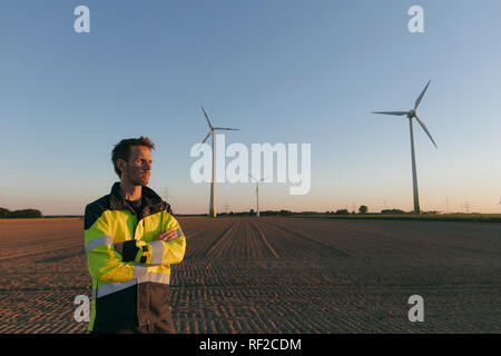 Engineer standing in a field at a wind farm - Stock Photo