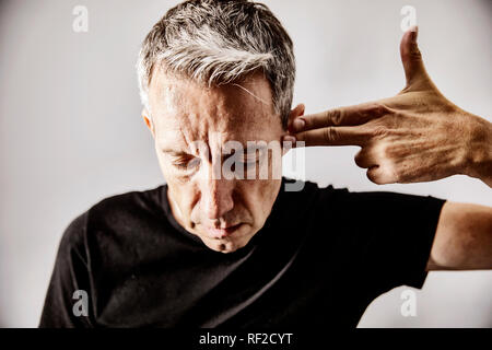 Portrait of mature man making shooting gesture with his hand against his temple - Stock Photo