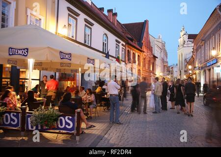 Restaurants and bars on Pilies Gatve street at night in the historic city centre of Vilnius, Lithuania, Baltic States - Stock Photo