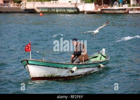 Fisherman in a boat on the Bosporus, Istanbul, Turkey - Stock Photo