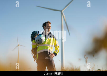 Technician standing in a field at a wind farm with climbing equipment - Stock Photo