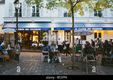 PARIS, FRANCE - NOVEMBER 9, 2018 - Cozy street with cafe and painters in Montmartre, Paris - Stock Photo