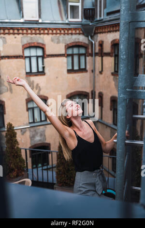 Happy young woman on balcony clambering a fire escape - Stock Photo