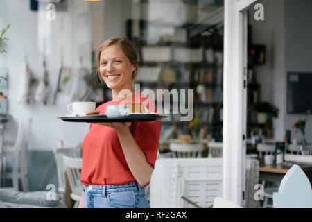 Portrait of smiling young woman serving coffee and cake in a cafe - Stock Photo