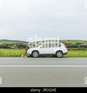 woman stand at roadside near broken car with opened hood. accident on the road - Stock Photo