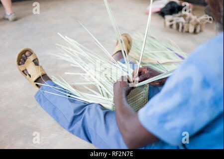 A Malawian man weaves baskets as part of a community outreach program of Majete Wildlife Reserve in Malawi; local communities craft souvenirs to sell - Stock Photo