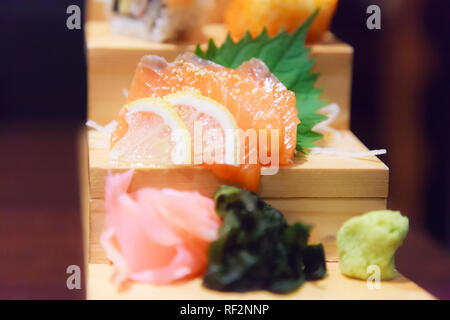 Japanese Fresh Fish Food Dish Menu,  Salmon Sashimi, seaweed, ginger and wasabi decorated on wooden step in traditional Japanese Restaurant. Healthy F - Stock Photo