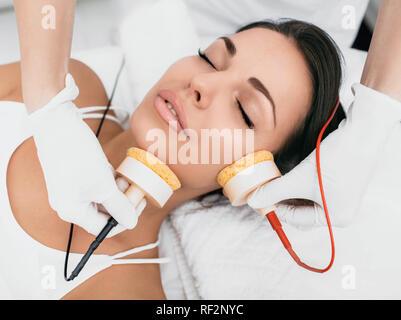 Beautiful woman receiving facial microcurrent procedure for lifting skin. - Stock Photo