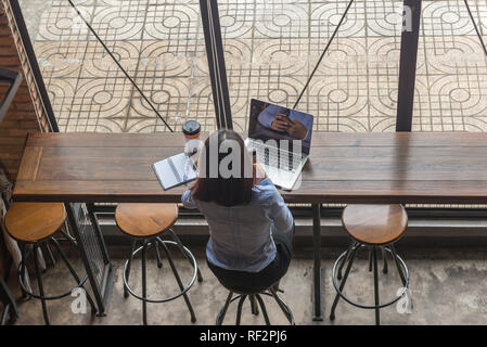 Rear view photo of Asian businesswoman checking email on phone - Stock Photo