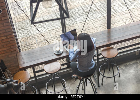 Rear view photo of Asian woman working on laptop - Stock Photo