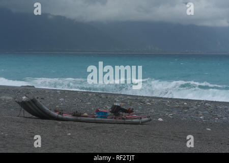 Small plastic raft, clear azure waters washing over pebble beach with Central Mountain Range on background, Chisingtan Scenic Area, Hualien, Taiwan - Stock Photo