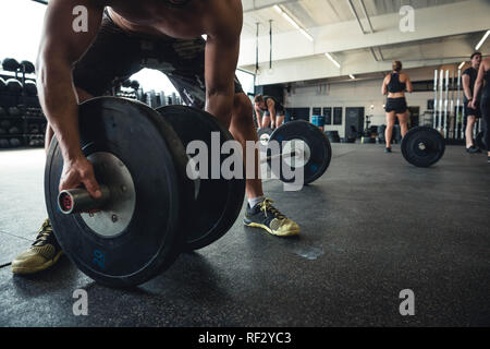 Authentic photos of men and women working out in gym setting. Gym equipment being used. - Stock Photo