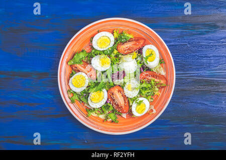 Fresh healthy salad with lettuce, eggs, tomatoes and sesame in orange plate on dark blue wooden surface. Top view, copy space. - Stock Photo