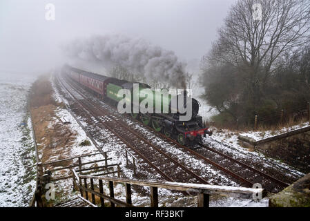 Austwick, North Yorkshire. 24th Jan 2019. UK Weather: B1 Class steam locomotive number 61306 on a test run from 'Steamtown' depot, Carnforth, Lancashire. Seen here in foggy Winter weather with snow on the ground, on the mainline near Austwick, North Yorkshire. Credit: John Bentley/Alamy Live News - Stock Photo