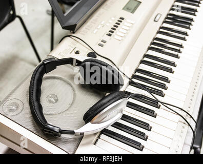 Headphones are resting on the speakers of an electric piano. - Stock Photo