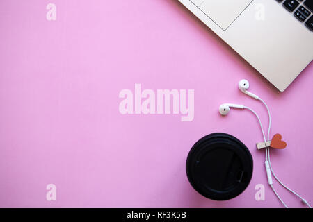 Workspace in pink trendy color. Laptop, glass of coffee and headphones nearby. Beginning of the holiday or the onset of Valentine's Day or another love event. Near there is a place for text. - Stock Photo