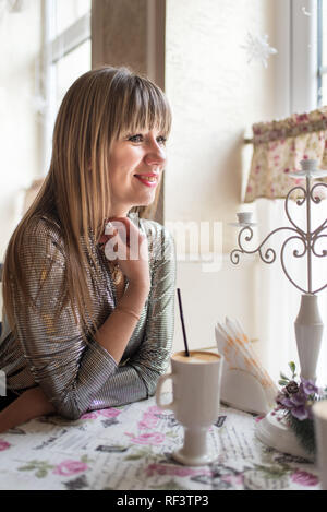 Beautiful young women sits at the table in cozy cafe and enjoys fragrant latte. Smile and positive emotions on her face. - Stock Photo