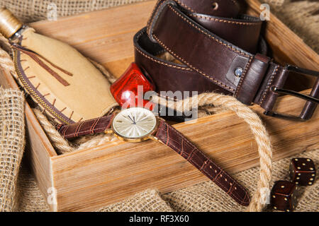 Men's accessories with brown leather belt, sunglasses, watch, smoking pipe and bottle with perfume on rustic background. - Stock Photo