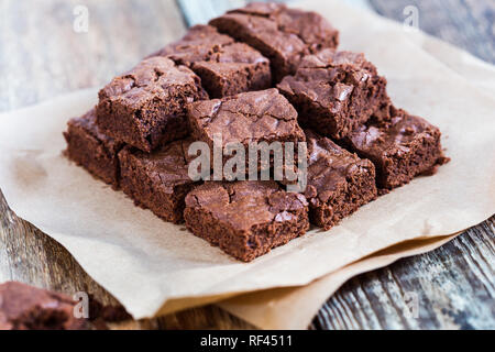 Pieces of freshly baked chocolate brownie on rustic wooden board, close-up, selective focus - Stock Photo