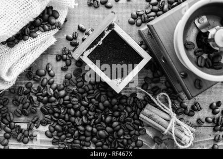 Manual coffee grinder on wooden table top view in black and white - Stock Photo