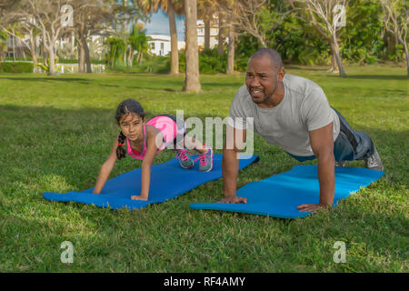 Father and daughter exercise together in the mornings. The young child follows her dads lead by doing pushups with him. - Stock Photo