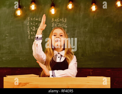answer. i know the answer. answer to any question. girl hold raised hand because she knows the answer. - Stock Photo