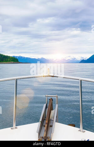 Motor crusing yacht in Glacier Bay National Park, Alaska. Sunset view of distant islands and snow-capped mountains over the bow of a motorboat. - Stock Photo
